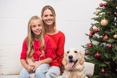 Familie met hond bij Kerstmisboom Stock Foto's