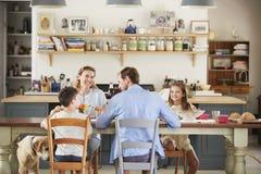 Familie met hond die samen bij de lijst in keuken eten stock afbeelding