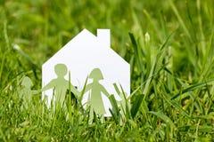 Familie met huis in een groen gras Stock Foto