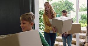 Familie met karton, dozen die in een comfortabel huis 4k binnengaan stock videobeelden