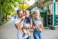 Familie met kind het lopen in het park stock afbeeldingen
