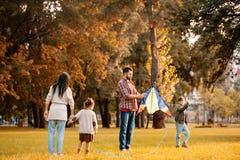 Familie met kinderen die een vlieger in proberen te vliegen royalty-vrije stock afbeelding