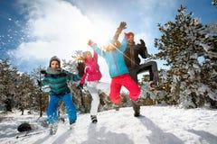 Familie met kinderenhoogspringen op de winterdag op skivakantie en Stock Foto's