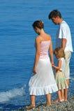 Familie met klein meisje op kust Royalty-vrije Stock Foto's