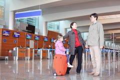 Familie met koffer die zich in luchthavenzaal bevindt royalty-vrije stock afbeelding