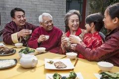 Familie met koppen het opgeheven roosteren over een Chinese maaltijd Stock Fotografie