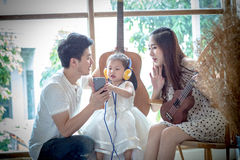Familie met meisje in Listen aan muziek op uw telefoon Royalty-vrije Stock Foto