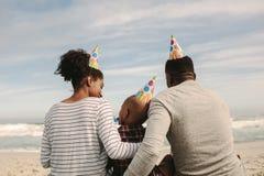 Familie met partijhoeden die fluitje op het strand blazen stock fotografie