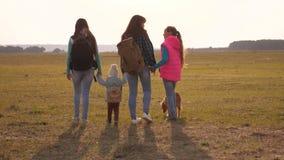 Familie met rugzakkenreizen met een hond groepswerk van een hechte familie moeder, dochters en van huishuisdieren toeristen stock footage