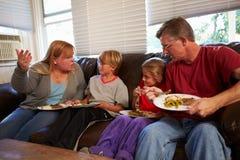 Familie met Slecht Dieet Sit On Sofa Eating Meal en het Debatteren stock afbeelding
