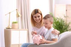 Familie met spaarvarken en geld Ruimte voor tekst stock afbeelding