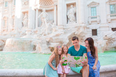 Familie met toeristische kaart dichtbij Fontana Di Trevi, Rome, Italië De gelukkige vader en de jonge geitjes genieten binnen van royalty-vrije stock afbeeldingen