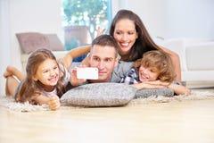 Familie met twee jonge geitjes die smartphone nemen selfie Royalty-vrije Stock Afbeeldingen