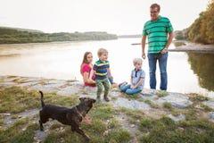 Familie met twee jongens bij het meer, zonnige de lentedag Royalty-vrije Stock Afbeelding