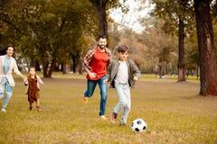 Familie met twee kinderen die en voetbal samen in in werking stellen spelen stock foto