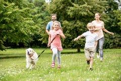 Familie met twee kinderen en hond stock fotografie