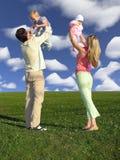 Familie met twee kinderen op blauwe hemel met wolken Royalty-vrije Stock Foto