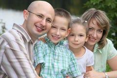 Familie met twee kinderen in park dichtbij vijver Stock Fotografie