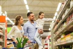 Familie met voedsel in boodschappenwagentje bij kruidenierswinkelopslag Stock Fotografie