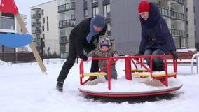 Familie met weinig schommeling van het babyspel in speelplaats bij de winter 4K stock footage