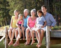 Familie mit 3 Erzeugungen, die Spaß durch einen See hat lizenzfreie stockfotografie