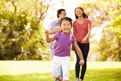 Familie mit Baby in der Träger, die durch Park geht Stockfoto