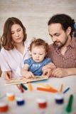 Familie mit Baby-Lesebuch zusammen Lizenzfreie Stockbilder
