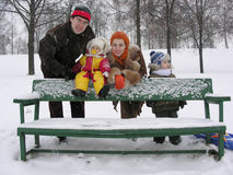 Familie mit Bank. Winter Stockbilder
