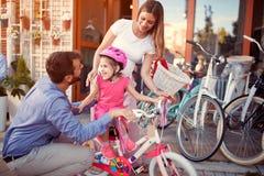 Familie mit dem glücklichen Kind, das kaufendes neues Fahrrad und Sturzhelme des Spaßes im Freien hat stockbild