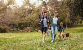 Familie mit dem Hund, der auf Picknick im Park geht stockbilder