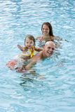 Familie mit dem jungen Kind, das im Swimmingpool spielt Stockfoto