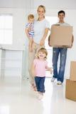 Familie mit dem Kasten, der in das neue Hauptlächeln sich bewegt Stockfoto