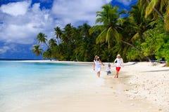 Familie mit dem Kind, das auf Strand spielt Lizenzfreie Stockbilder