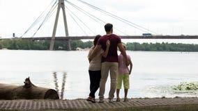 Familie mit dem Kind, das Brücke, Konzept der Immigration betrachtet oder auf neue Stadt sich bewegt lizenzfreie stockfotografie