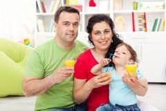 Familie mit dem Kind, das Fruchtsaft isst Stockfotos