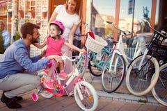 Familie mit dem Kind, das kaufendes neues Fahrrad und Sturzhelme des Spaßes im Freien hat stockbild