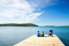 Familie mit dem kleinen Baby, das auf Pier nahe dem Meer sitzt Stockfoto