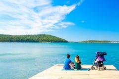Familie mit dem kleinen Baby, das auf Pier nahe dem Meer sitzt Lizenzfreie Stockfotografie