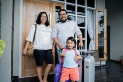 Familie mit dem Koffer, der vor ihrem Haus steht stockfotografie