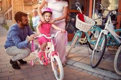 Familie mit dem M?dchen, das kaufendes neues Fahrrad und Sturzhelme des Spa?es im Freien hat stockfotografie