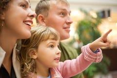 Familie mit dem Mädchen mit der Hand Finger vorwärts zeigend Stockfotografie