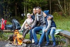 Familie mit dem Smartphone, der selfie nahe Lagerfeuer nimmt Stockfotos