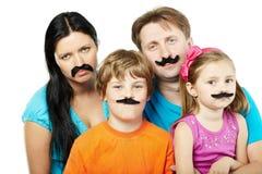 Familie mit den geklebten künstlichen Schnurrbärten. Stockbild