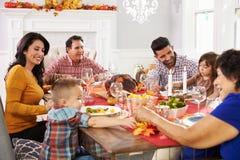 Familie mit den Großeltern, die bei Tisch Danksagungs-Mahlzeit genießen Stockbild