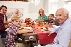 Familie mit den Großeltern, die bei Tisch Danksagungs-Mahlzeit genießen