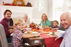 Familie mit den Großeltern, die bei Tisch Danksagungs-Mahlzeit genießen Stockfotos