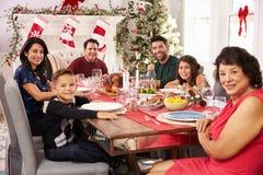 Familie mit den Großeltern, die bei Tisch Weihnachtsmahlzeit genießen Lizenzfreie Stockbilder