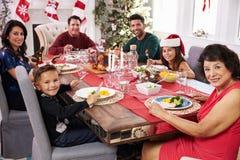Familie mit den Großeltern, die bei Tisch Weihnachtsmahlzeit genießen Stockbilder