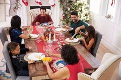 Familie mit den Großeltern, die bei Tisch Weihnachtsmahlzeit genießen Lizenzfreie Stockfotos