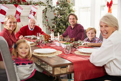 Familie mit den Großeltern, die bei Tisch Weihnachtsmahlzeit genießen Lizenzfreies Stockfoto